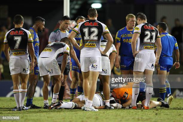 Sitaleki Akauola of the Panthers is attended to by trainers and medical staff after a tackle during the NRL Trial match between the Penrith Panthers...