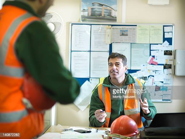 Site foreman advising apprentice in office of building site