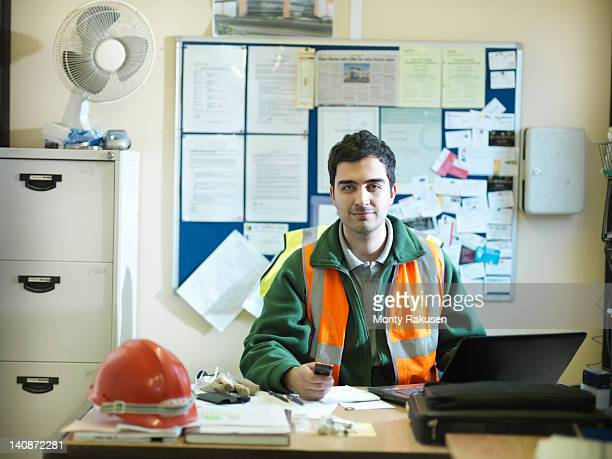 Site foreman at desk in office of building site