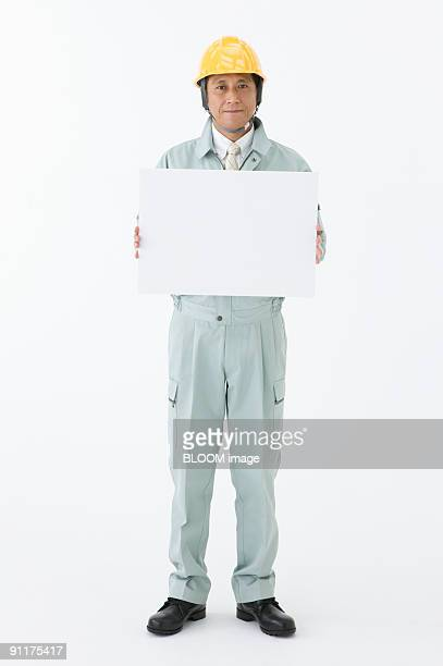 Site foreman holding white board, studio shot