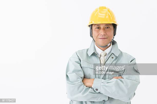 Site foreman with arms crossed, studio shot