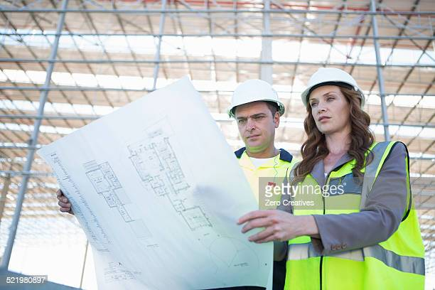 Site manager and architect looking down at blueprint on construction site
