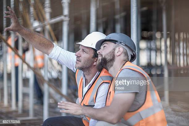 Site manager and builder looking up at steel rods on construction site