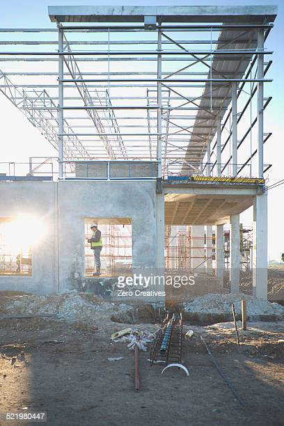 Site manager checking window frame on construction site