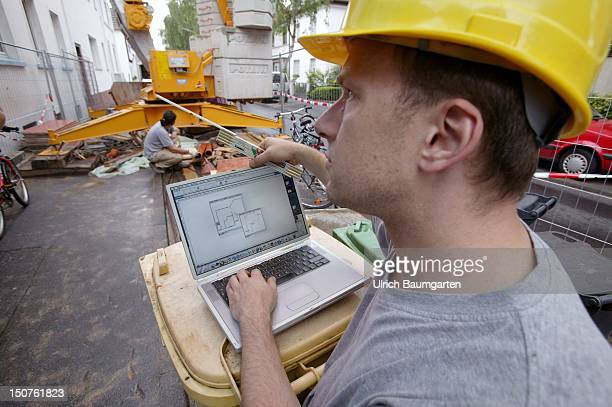 Site manager with blueprint on his notebook on a construction site