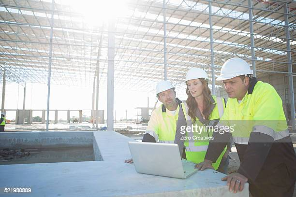 Site managers and architect looking at laptop on construction site