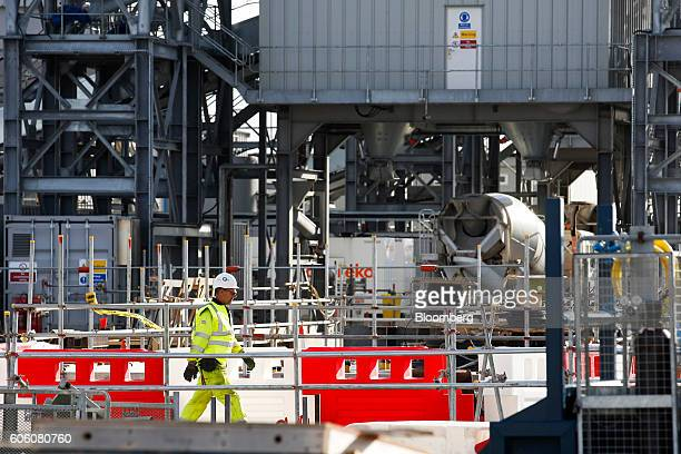 A site worker walks through the concrete batching plant at the Hinkley Point C nuclear power station operated by Electricite de France SA's near...