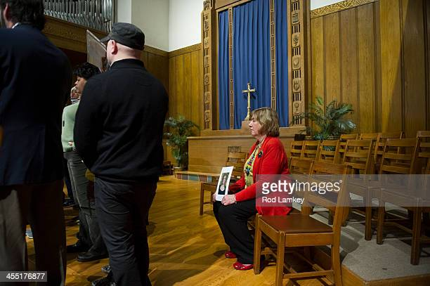 sits alone and holds a photo of her daughter Lauren Rousseau who was a substitute teacher when she was killed at Sandy Hook Elementary School nearly...