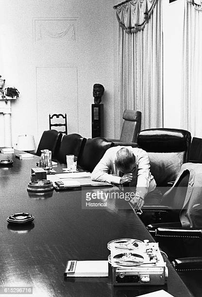 Sitting alone in the Cabinet Room President Lyndon B Johnson listens to a tape recorded message about the fighting in Vietnam The message is from his...