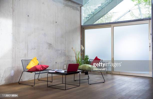 sitting area in a loft at concrete wall - indoors stock-fotos und bilder