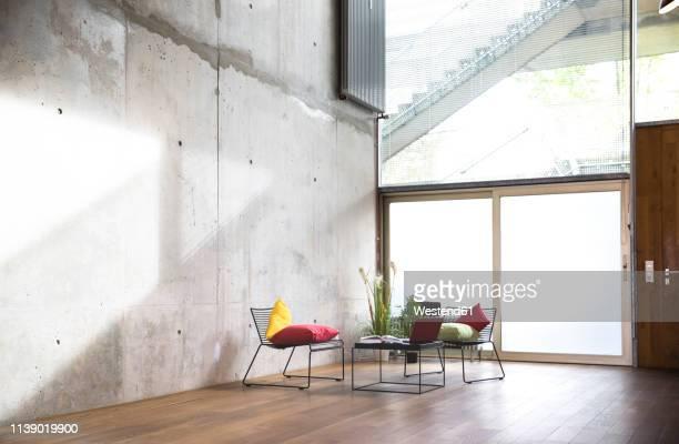 sitting area in a loft at concrete wall - imagen minimalista fotografías e imágenes de stock