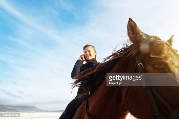 Sitting astride her horse, smiling woman talks on her cellphone
