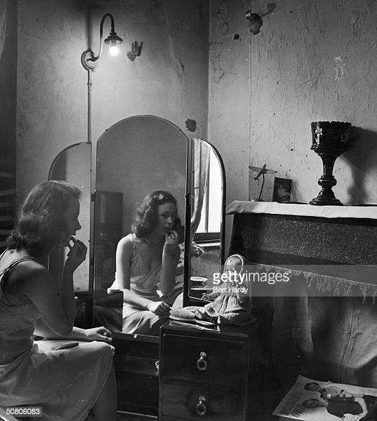 Sitting at her dressing table sixteen year old hairdresser Betty Burden applies her lipstick13th January 1951 She lives at home in a Birmingham slum...
