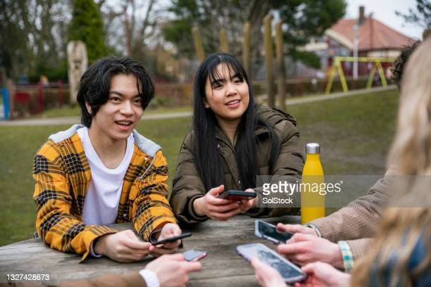 sitting at park table - alternative pose stock pictures, royalty-free photos & images