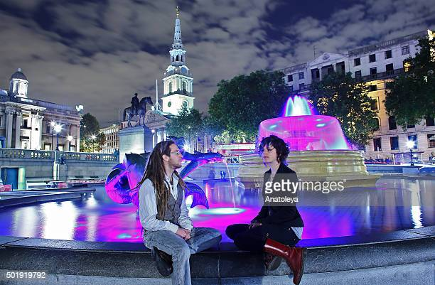 Sitting by a fountain at night