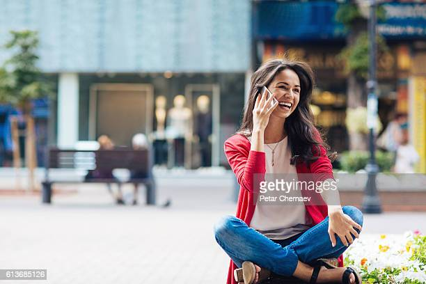 Sitting crosslegged on a bench and talking on the phone