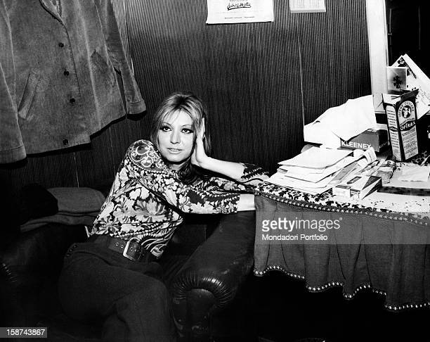 Sitting in a dressing room Italian singer and actress Alida Chelli born Alida Rustichelli poses left arm and head against the armrest of an armchair...