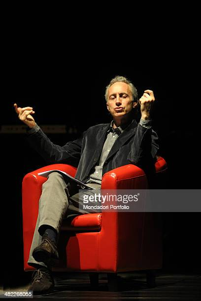 Sitting in a red armchair in the centre of the stage Marco Travaglio talks to the audience reading and arguing a piece with the nipping tones that...