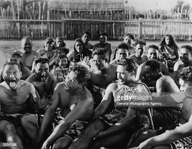 Sitting in a stockade a group of Maoris pull tongues a scene from 'Under The Southern Cross' A Universal Pictures film also known as 'The Devil's...