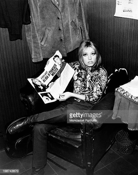 Sitting in an armchair Italian singer and actress Alida Chelli born Alida Rustichelli incredulously shows some review pages that report news about...