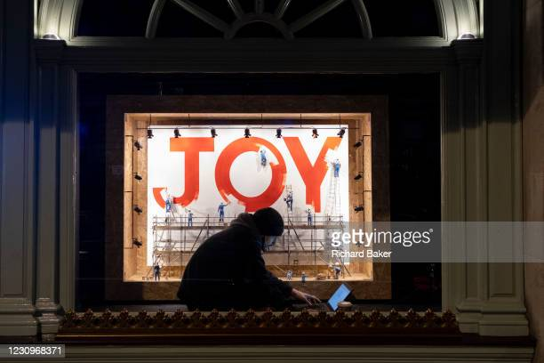 Sitting in front of a window display, a young man watches the screen of his laptop in the window of Fortnum and Mason on Piccadilly which features an...