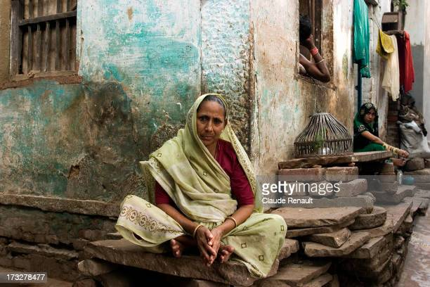 Sitting in front of her house in Vaaranasi, on the stone where she does her laundry