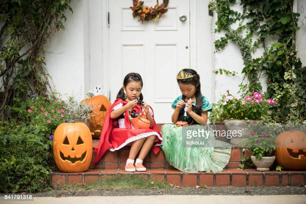 sitting in front of the house girls are eating sweets. - naughty halloween stock photos and pictures