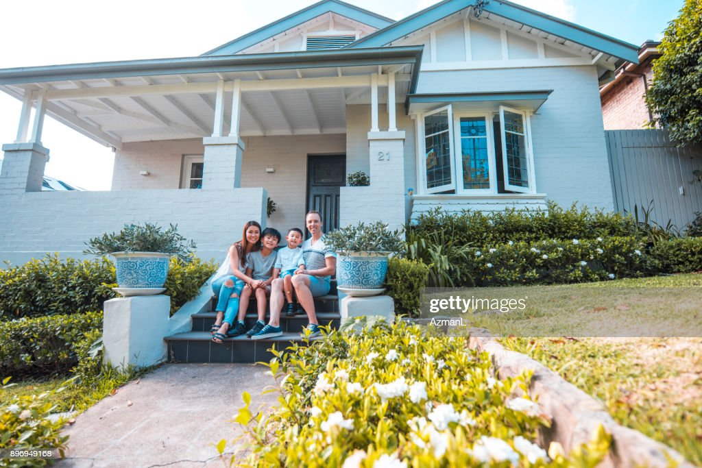 Sitting in front of their home : Stock Photo