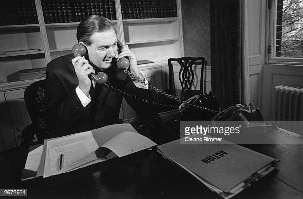 Sitting in his office, Chancellor of the Exchequer in the Labour government, James Callaghan answers two phones at once, on his desk a file marked...