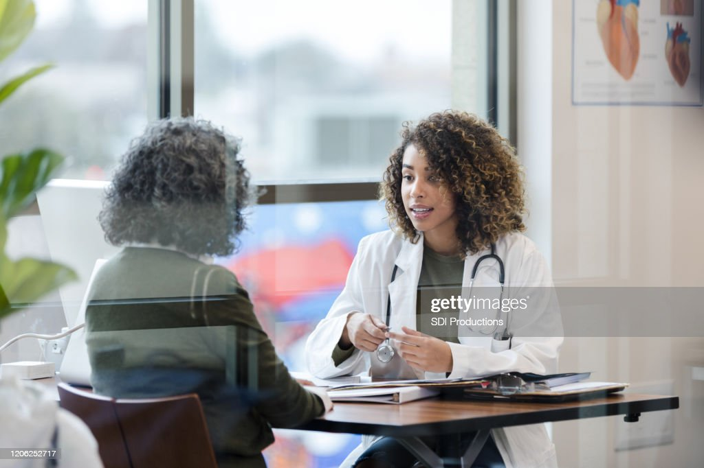 Sitting in office, doctor has serious conversation with patient : Stock Photo