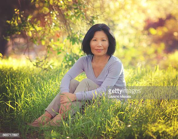 Sitting in sunlit grass - woman