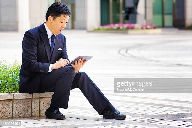 Sitting Japanese businessman surprised and shocked by tablet outdoors