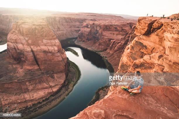 sentado cerca de la curva de herradura - gran cañon fotografías e imágenes de stock