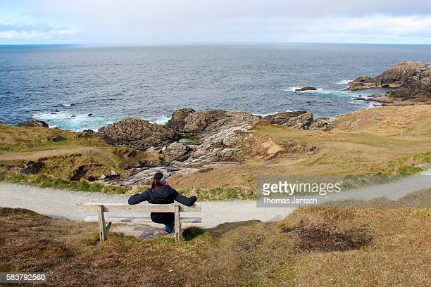 Sitting on a bench and looking at the rugged coast of Malin Head, Ireland