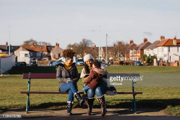 sitting on a bench with mum and grandma - whitley bay stock pictures, royalty-free photos & images