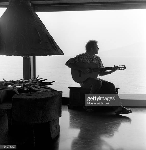 Sitting on a chest Apulian singersongwriter Domenico Modugno wields a guitar and wistfully looks towards the sea across a fulllength window 1964