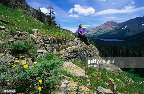 sitting on a rock at upper two medicine creek admiring the view of two medicine lake - glacier national park, montana - lago two medicine montana - fotografias e filmes do acervo