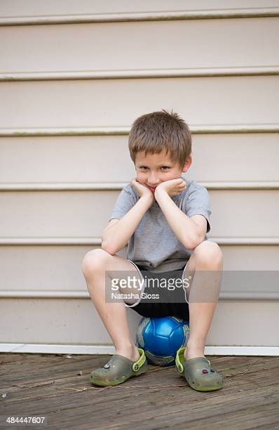 Sitting on a soccer ball, smiling