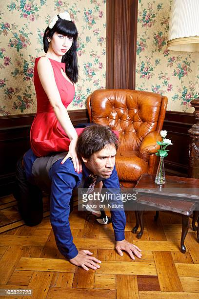 sitting on his back - women dominating men stock photos and pictures