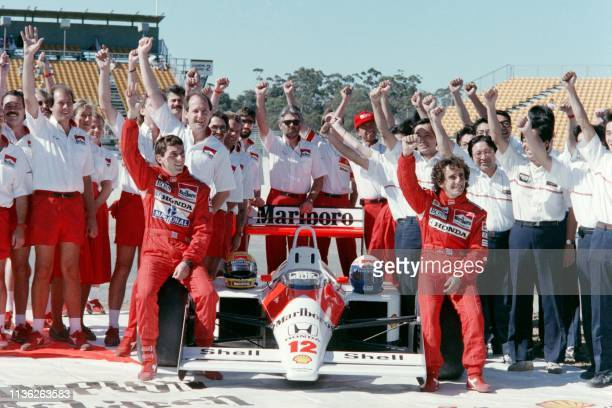 Sitting on his McLaren Honda, new world champion Ayrton Senna of Brazil raises his fist along with his team mate Alain Prost of France and all...