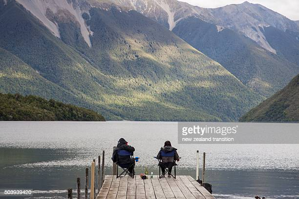 sitting on Lake Rotoiti jetty with view of St Arnaud Range, Nelson Lakes National Park, New Zealand