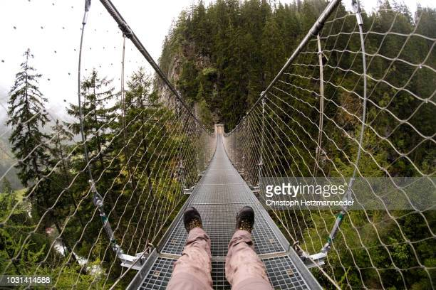 sitting on rope bridge - hängebrücke stock-fotos und bilder