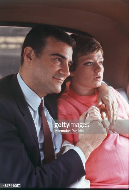 Sitting on the back seat of a car the Italian producer Teddy Reno born Ferruccio Merk Ricordi hugs tenderly his wife the Italian singer Rita Pavone...