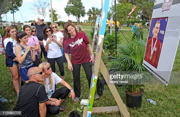 Sitting on the ground parents of slain Marjory Stoneman Douglas High School student Nicholas Dworet Mitch and Annika Dworet look at an art piece to...