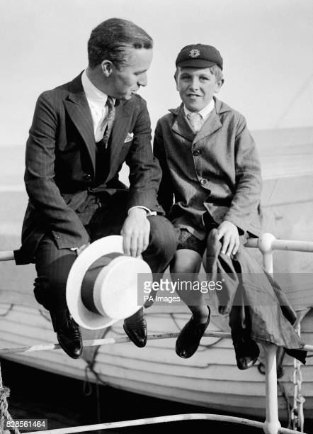 Sitting on the rail of the 'RMS Olympic' silent Charlie Chaplin chats to a young admirer as the ship prepares to dock in Southampton