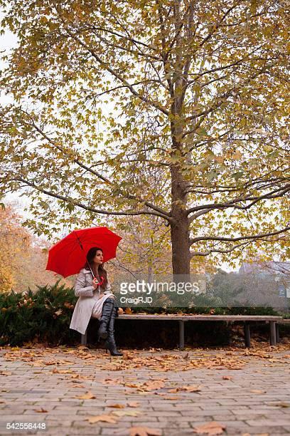 Unter einem Baum hockend im Herbst