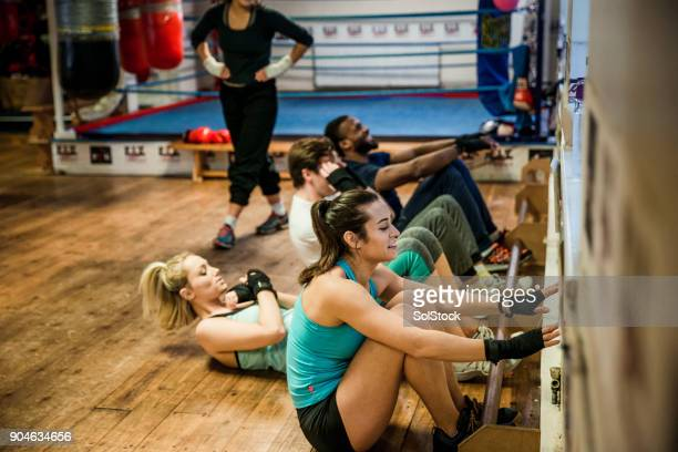sit-ups during a circuit training class - circuit training stock photos and pictures