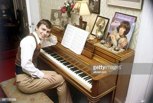 sitzt zu Hause in den USA am Klavier auf dem die LP seiner Mutter steht 'So war Alexandra' ohne Jahr