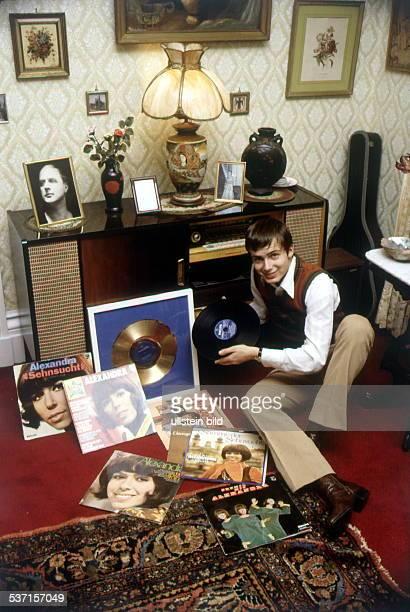 sitzt zu Hause in den USA auf dem Boden und schaut sich die LPs seiner Mutter Alexandra an ohne Jahr