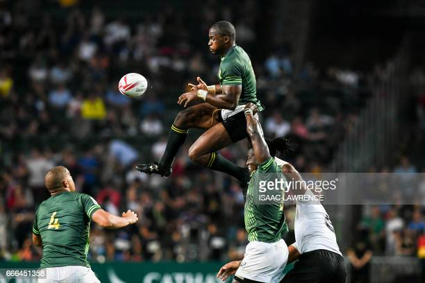 Siviwe Soyizwapi of South Africa is lifted to the ball by his teammate Tim Agaba during the Cup Final against Fiji on the third day of the Hong Kong...